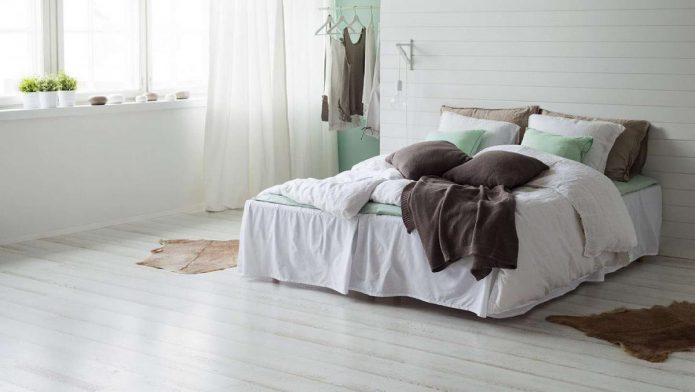 Спальня с белым лапинатом на полу и стенах