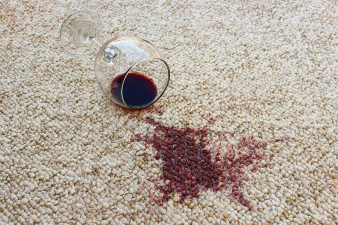 Бокал и разлитое вино на ковре
